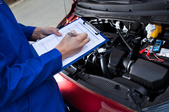 Midsection of mechanic holding clipboard in front of open car engine at street